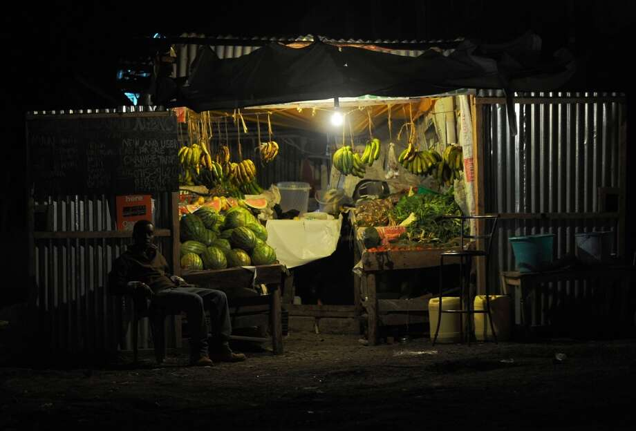Kenya: A fruit and vegetable vendor sits outside his stall in a suburb of Nairobi past dusk on April 18, 2014. Nairobi has in recent years seen an increasing trend by small scale businesses such as food and clothes hawkers as well as privately-run public transport providers operating well into or overnight in the hope of increasing their sales even as Kenya gears to achieve the key middle-income economic status next month following a government-led statistical review, likely to increase the size of the countrys economy by a fifth to $50bn. Photo: TONY KARUMBA, AFP/Getty Images
