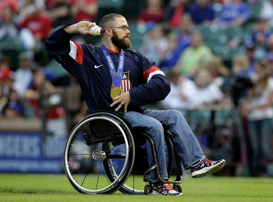 U.S. hockey Paralympic gold medalist Taylor Lipsett throws out the honorary first pitch before a baseball game between the Chicago White Sox and the Texas Rangers, Friday, April 18, 2014, in Arlington, Texas. (AP Photo/Tony Gutierrez) Photo: Tony Gutierrez, Associated Press / AP