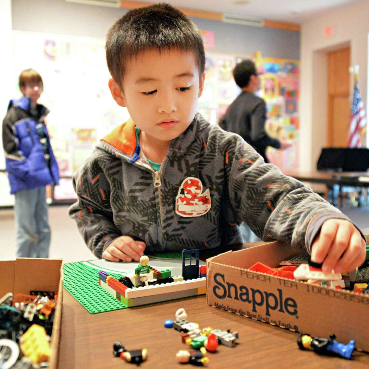 Six-year-old James Gong of Guilderland digs through a box of Lego parts during a Lego building for tweens program at the Guilderland Public Library Friday, April 18, 2014, in Schenectady, N.Y. (John Carl D'Annibale / Times Union)