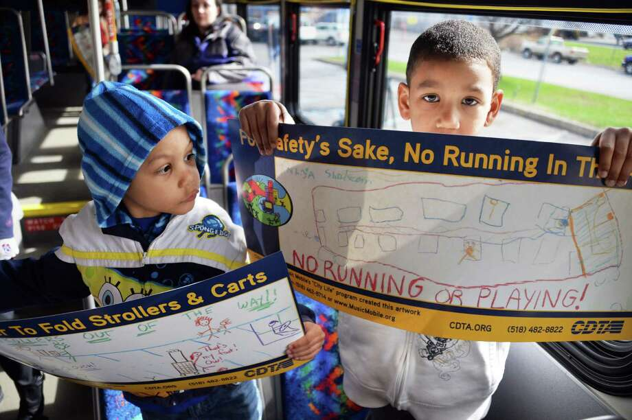 Brothers Zaire, 3, left, and Shakeem Miller, 5, of Albany, hold posters, part of a Music Mobile partnership with CDTA to promote bus safety held Friday morning, April 18, 2014, in Albany, N.Y. The posters will begin to appear on CDTA buses by the end of April. (John Carl D'Annibale / Times Union) Photo: John Carl D'Annibale / 00026546A