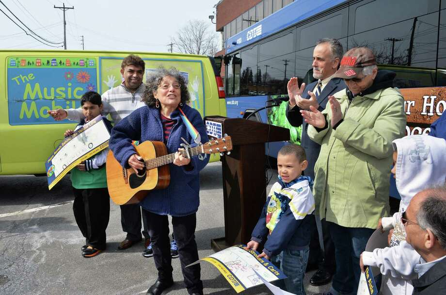 Music Mobile executive director Ruth Pelham, center, plays her guitar as children attending the Music Mobile's City of Life program sing during a news conference announcing a partnership with CDTA to promote bus safety Friday, April 18, 2014, in Albany, N.Y. (John Carl D'Annibale / Times Union) Photo: John Carl D'Annibale / 00026546A