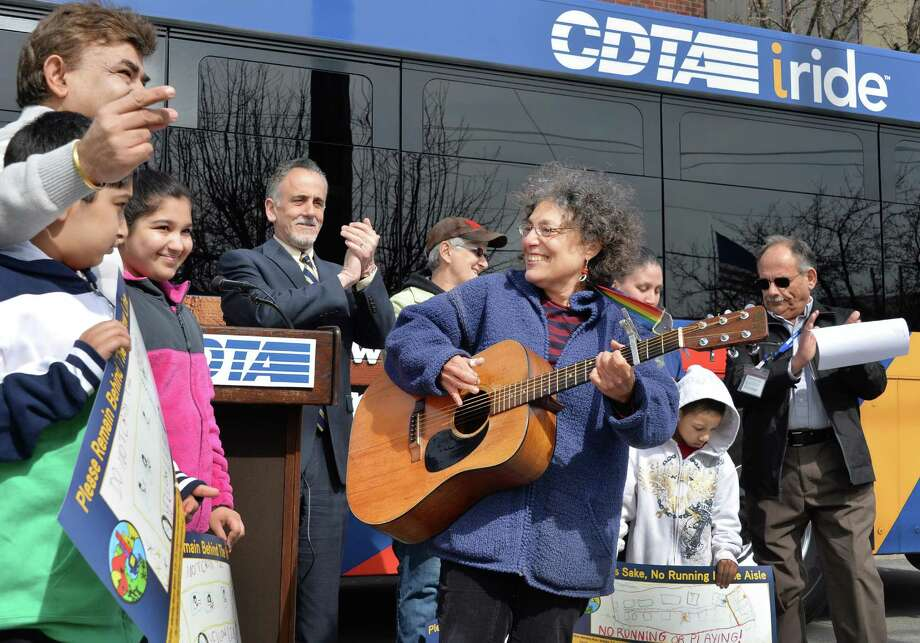 Music Mobile executive director Ruth Pelham, center, plays her guitar as children attending the Music Mobile's City of Life program sing during a news conference announcing a partnership with CDTA to promote bus safety Friday moring, April 18, 2014, in Albany, N.Y. (John Carl D'Annibale / Times Union) Photo: John Carl D'Annibale / 00026546A