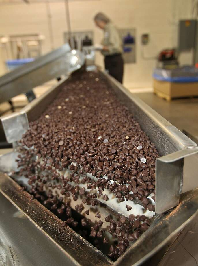 Chocolate chips fall into a hopper at a plant run by Blommer, the largest U.S. bean processor. Photo: Michael Bryant, McClatchy-Tribune News Service