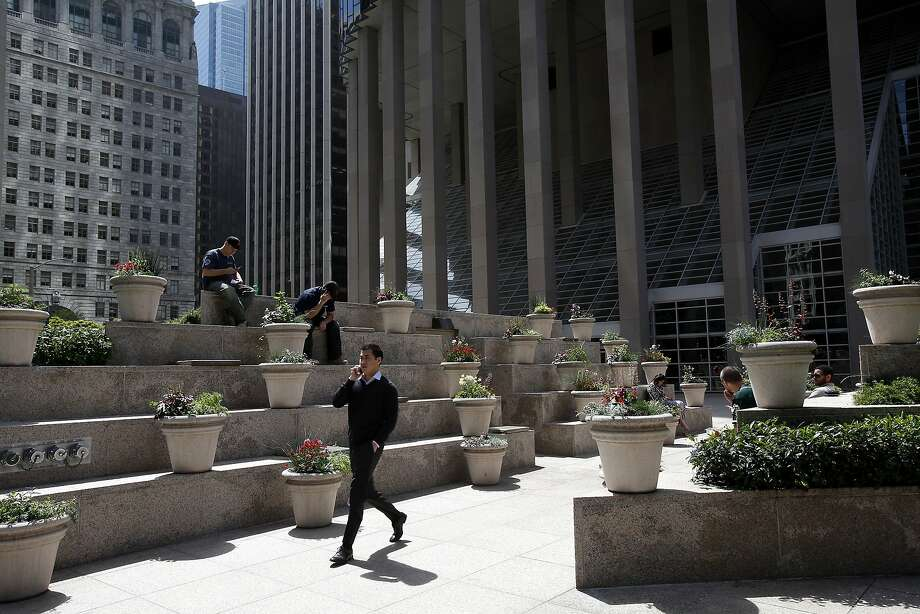 People enjoy the sun around lunchtime in the public plaza at the corner of California and Davis streets in the Financial District despite being surrounded by tall buildings and concrete, a bit like New York City. Photo: Sarah Rice, Special To The Chronicle