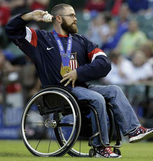 U.S. hockey Paralympic gold medalist Taylor Lipsett throws out the honorary first pitch before a bas