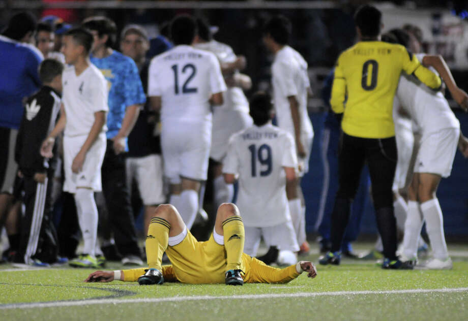 Exhausted Houston Lee senior midfielder Abraham Miron lays on the turf as the Pharr Valley View Tigers celebrate their 4-1 win over the Generals in the Class 4A Boys State Soccer Semifinal game at Birkelbach Field in Georgetown on Friday. Photo: Jerry Baker, For The Chronicle