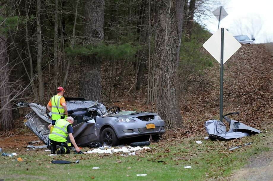 Emergency workers look over a Mazda that was involved in a fatal crash on Friday, April 18, 2014, on Burgoyne Road in the Town of Saratoga, N.Y. (Cindy Schultz / Times Union) Photo: Cindy Schultz / 00026562A