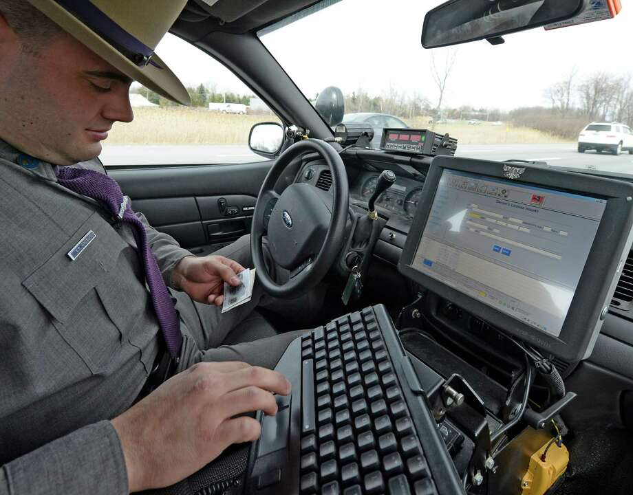 Trooper Emmett Kinzel checks a license and registration after a vehicle is stopped for excessive speed as he participates in a week-long enforcement initiative targeting speeding and aggressive drivers across the state Friday afternoon, April 18, 2014, on I-87 in Colonie, N.Y.  The Speed Week campaign runs from April 17 through April 24, 2014. Fines for speeding and aggressive driving can reach nearly $1,000 and add up to 11 points on a driver's license. (Skip Dickstein / Times Union) Photo: Skip Dickstein / 00026558A