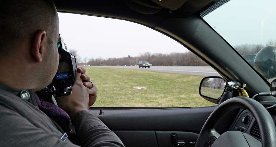 Trooper Emmett Kinzel uses a radar gun to track a vehicle  for excessive speed as he participates in a week-long enforcement initiative targeting speeding and aggressive drivers across the state Friday afternoon, April 18, 2014, on I-87 in Colonie, N.Y.  The Speed Week campaign runs from April 17 through April 24, 2014. Fines for speeding and aggressive driving can reach nearly $1,000 and add up to 11 points on a driver's license. (Skip Dickstein / Times Union) Photo: Skip Dickstein / 00026558A