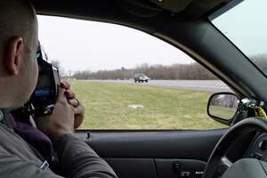 Trooper Emmett Kinzel uses a radar gun to track a vehicle  for excessive speed as he participates in a week-long enforcement initiative targeting speeding and aggressive drivers across the state Friday afternoon, April 18, 2014, on I-87 in Colonie, N.Y.  The Speed Week campaign runs from April 17 through April 24, 2014. Fines for speeding and aggressive driving can reach nearly $1,000 and add up to 11 points on a driver's license. (Skip Dickstein / Times Union)
