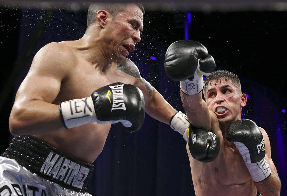 San Antonio's Raul Martinez (left) and Sergio Perales exchange punches during their junior featherweight bout Friday night at the Alamodome's Illusions Theater. Perales won in an upset. Photo: Edward A. Ornelas / San Antonio Express-News / ©2014 San Antonio Express-News