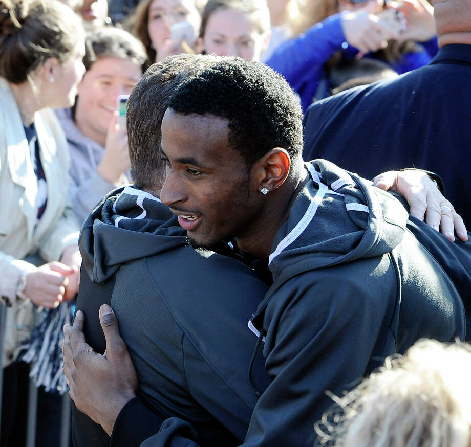 Connecticut men's basketball player DeAndre Daniels, right, hugs Connecticut women's head coach Geno Auriemma after Auriemma arrived on campus with his team for a rally celebrating their NCAA title on Wednesday, April 9, 2014, in Storrs, Conn. Photo: Jessica Hill, AP / Associated Press