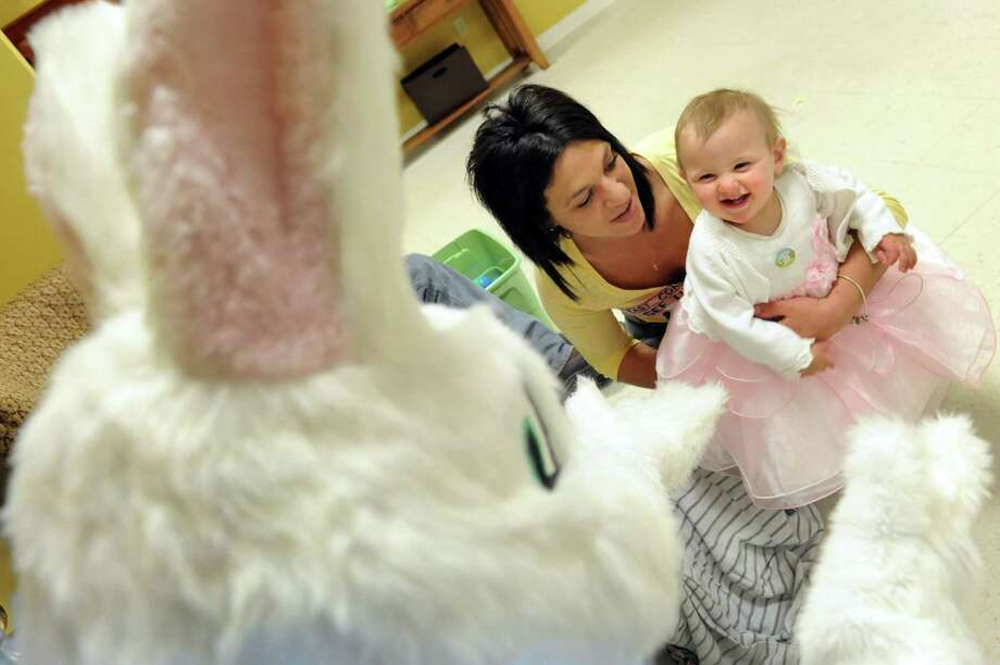 Beige Sawyer, 10 months, right, delights in meeting the Easter Bunny on Saturday, April 19, 2014, at the Senior Citizens Center in Watervliet, N.Y. Joining Beige is her mother, Kelly Garrison. (Cindy Schultz / Times Union) Photo: Cindy Schultz / 00026458A
