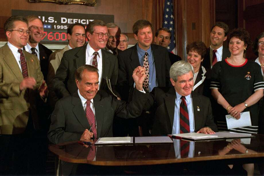 Bob Dole, left, and House Speaker Newt Gingrich clasped hands during a Capitol Hill news conference in 1995 to sign the Republican's budget resolution. Gingrich's plan retained the spending cuts and tax increases from Bush's 1990 budget agreement. Photo: DENNIS COOK, STF / AP