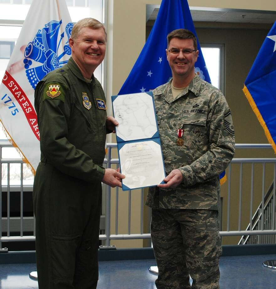 Air National Guard New York Air National Guard Commander Major General Verle Johnston presents a Meritorious Service Medal and Citation to Senior Master Sgt. Robert Bolger during a ceremony in Latham.