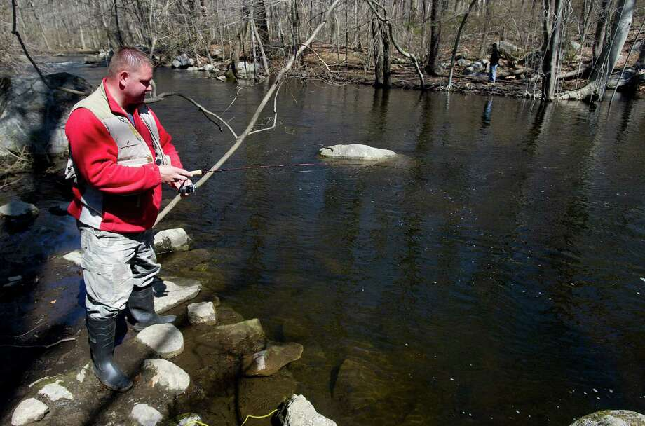 Mariusz Borowski, a Stratford resident who works in Greenwich, fishes in the Mianus River on the Stamford and Greenwich border on Saturday, April 19, 2014, the opening day of trout season. Photo: Lindsay Perry / Stamford Advocate