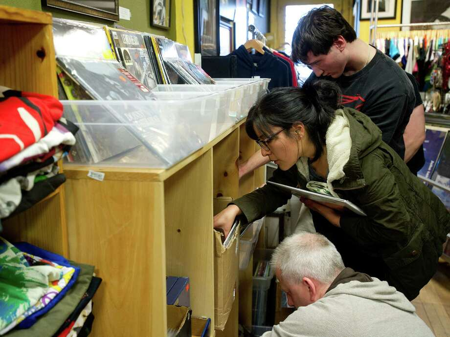 Anthony Smith of Easton, top, and Gianina Venegas of Greenwich, center, look through albums at Johnny's in Darien, Conn., during Record Store Day on Saturday, April 19, 2014. Record Store Day started in 2008 and takes place the third Saturday of April every year, when artists release records available only on that day and only in independent, brick and mortar record stores. Photo: Lindsay Perry / Stamford Advocate