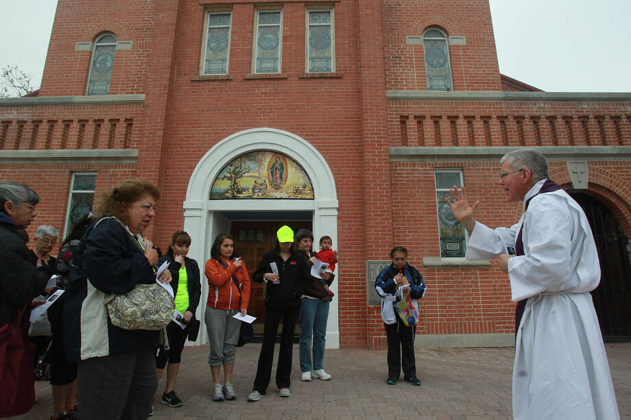 Father James Marshall (right) blesses a group of people Thursday April 17, 2014 in front of Our Lady of Guadalupe Catholic Church at 1321 El Paso street on San Antonio's West Side. The group gathers each year to visit seven local churches by traveling on foot to each of the churches. Led by Jo Ann Ruiz, the group prays for God's blessing on Easter and in the coming year. Photo: JOHN DAVENPORT, San Antonio Express-News / ©San Antonio Express-News/John Davenport