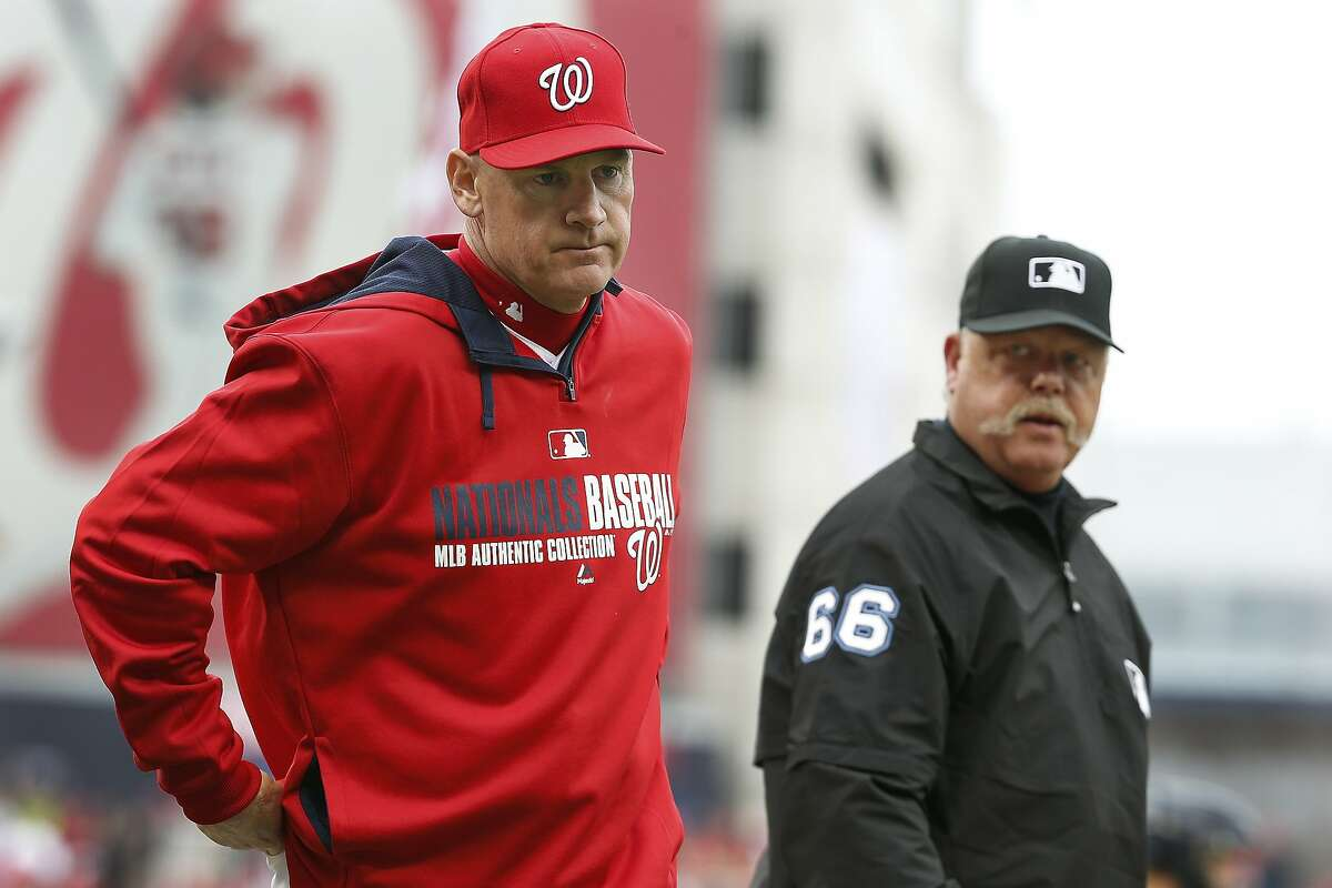 Washington Nationals manager Matt Williams (9) walks back to the dugout after being informed by umpire Jim Joyce (66) that Ian Desmond's inside-the-park homer was overturned on replay review and changed to a ground-rule double during the fifth inning of a baseball home opener the Atlanta Braves at Nationals Park Friday, April 4, 2014, in Washington. (AP Photo/Alex Brandon)