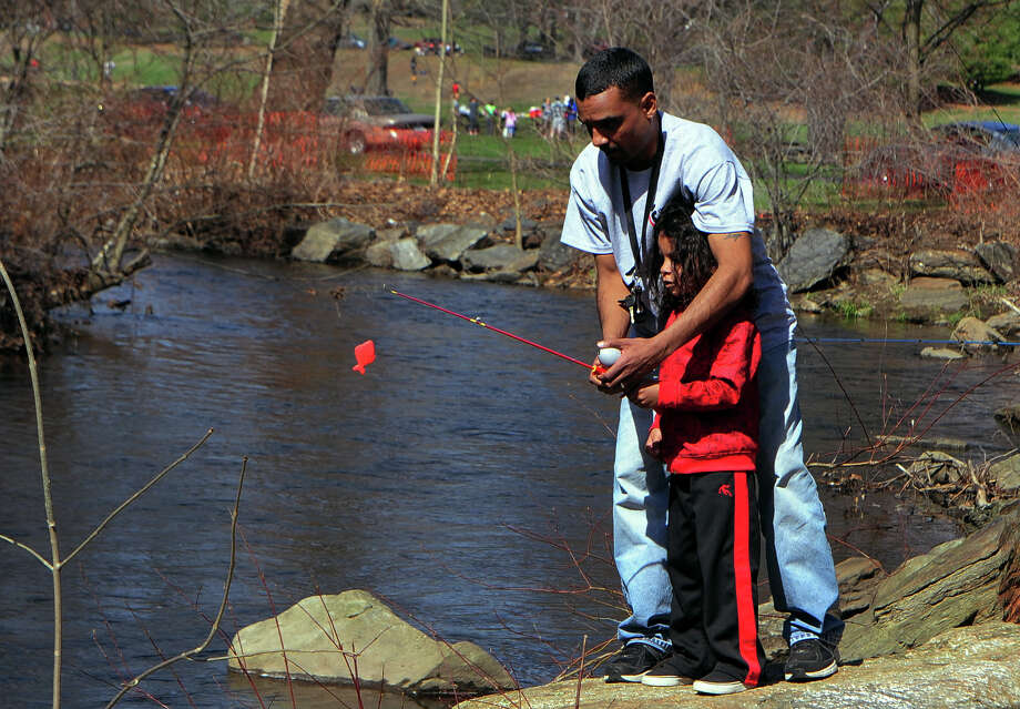 Tony Bermudez helps teach his son Ito, 4, how to cast a line during opening day of trout fishing at Beardsley Park in Bridgeport, Conn. on Saturday April 19, 2014. Photo: Christian Abraham / Connecticut Post