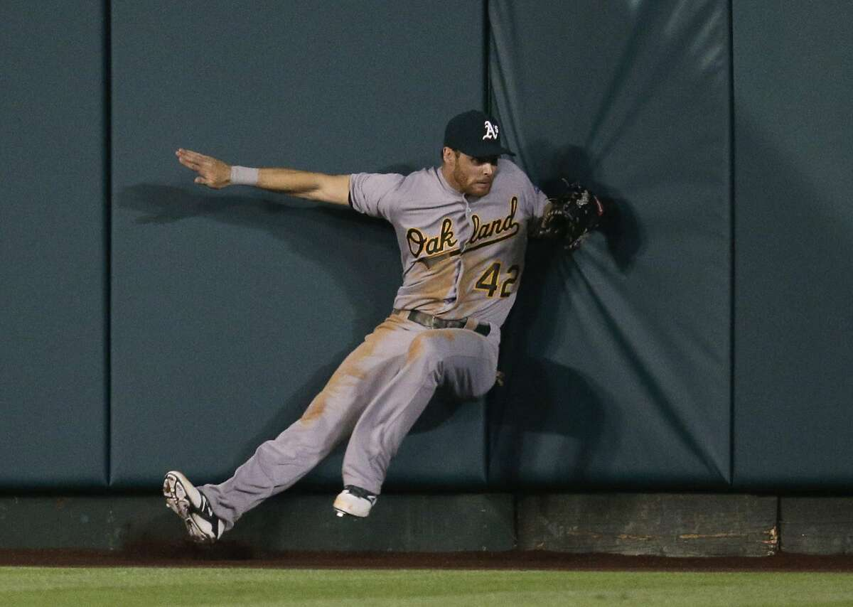 Oakland Athletics' Craig Gentry hits the wall after catching a fly ball hit by Los Angeles Angels' Albert Pujols during the seventh inning of a baseball game on Tuesday, April 15, 2014, in Anaheim, Calif. (AP Photo/Jae C. Hong)
