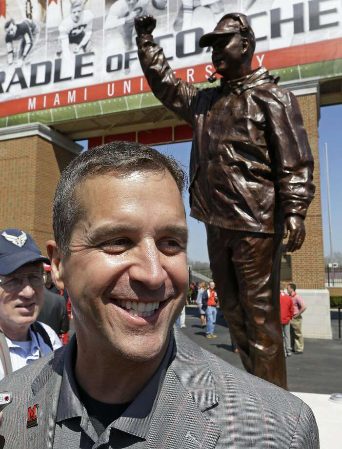John Harbaugh poses in front of the bronze statue of him that was unveiled at his alma mater, Miami University in Ohio. Photo: Al Behrman, Associated Press