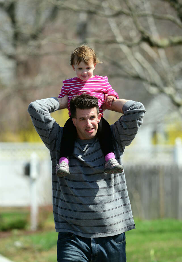 Ryan Egan, of Fairfield, carries his daughter Ellie, 2, on his shoulders as he walks along Glendale Road in Stratford, Conn. on Saturday April 19, 2014. They came to visit Ellie's grandfather Mike DeMarky, who lives in Stratford. Photo: Christian Abraham / Connecticut Post