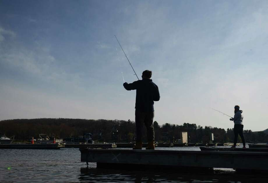 Lenny Meldon, left, of Brookfield, and Fallon Negro, of Brewster, N.Y., fish off the dock of Echo Bay Marina on Candlewood Lake in Brookfield, Conn. Saturday, April 19, 2014.  Fishermen flocked to the lakes and streams for the opening day of fishing season Saturday. Photo: Tyler Sizemore / The News-Times