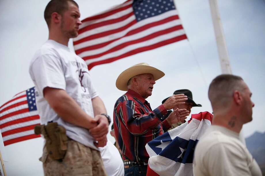 Schuyler Barbeau, left, is pictured near rancher Cliven Bundy during a 2014 standoff at Bundy's Nevada ranch. Barbeau pleaded guilty Tuesday to federal gun crimes. (AP Photo/Las Vegas Review-Journal, John Locher) Photo: John Locher, MBR / Las Vegas Review-Journal