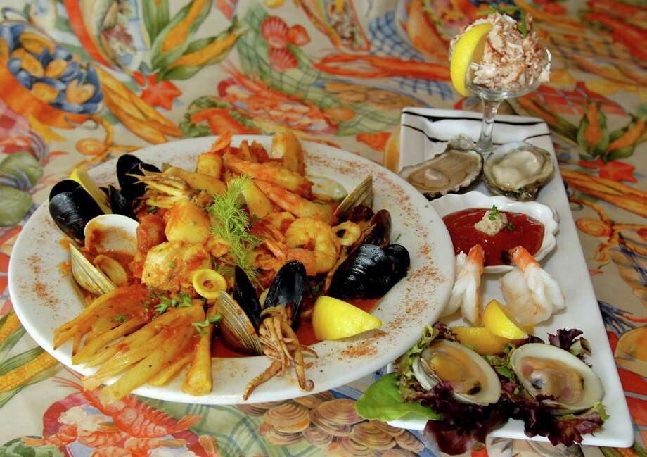 Salty's Pub & Bistro, 215 Guideboard Rd., Clifton Park, NY, 518-371-1120. The San Francisco Cioppino with fresh haddock, jumbo shrimp scallops, little neck clams, calamari, and mussels all braised with fresh tomatoes, white wine, garlic, capers, roasted fennel & saffron. On the long plate, shrimp, clams, oysters, crab served with cocktail sauce & fresh lemon. (Luanne Ferris/Times Union) Visit Web site.  Photo: LMF, DG / ALBANY TIMES UNION