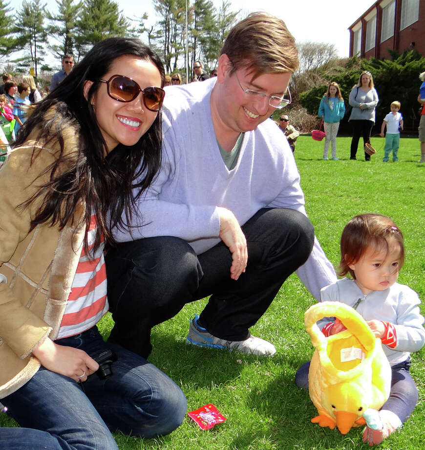 Enjoying a bright spring Saturday at the Greens Farms Volunteer Fire Co. egg hunt are Amy Yan, Sean Grettum and young Jacqueline Grettum of Westport. Photo: Mike Lauterborn / Westport News