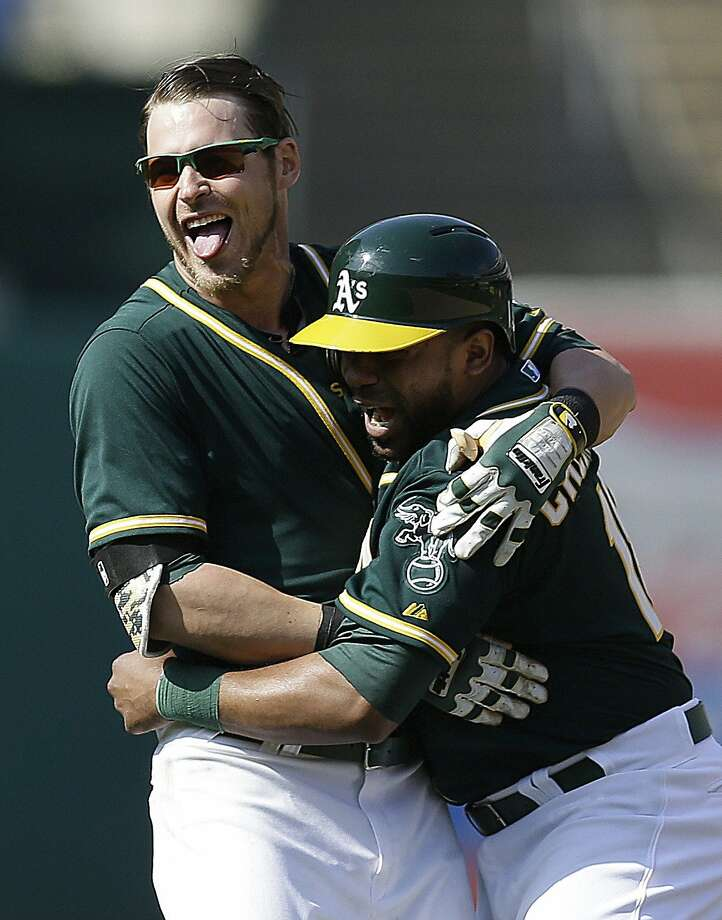 Josh Reddick (left) celebrates with Alberto Callaspo after the win. Photo: Ben Margot, Associated Press