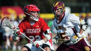 Greenwich high school's Ryan Flippin looks for a teammate to pass to as St Joseph high school defenseman Shane Miller covers him during a boy's lacrosse game played at St Joseph high school, Trumbull, CT on Saturday, April, 19th, 2014.