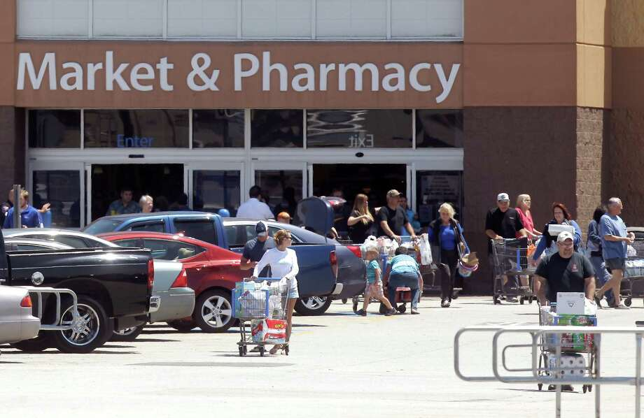 Customers leave the Wal-Mart shopping center after being kept inside for four hours while FBI bomb squad and Kemah police investigated a suspicious device in the parking lot on Saturday, April 19, 2014, in Kemah. Photo: J. Patric Schneider, For The Chronicle / © 2014 Houston Chronicle