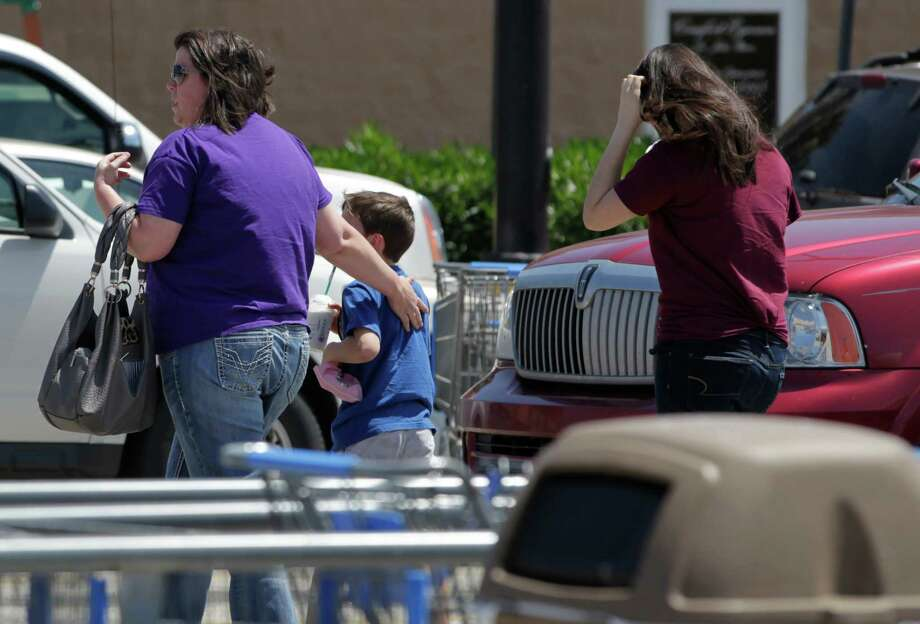 Customers walk the Wal-Mart shopping center parking lot after FBI bomb squad and Kemah police investigated a suspicious device on Saturday, April 19, 2014, in Kemah. Photo: J. Patric Schneider, For The Chronicle / © 2014 Houston Chronicle