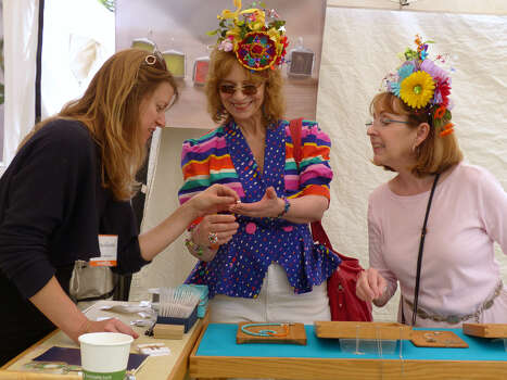 Kristin Warnson, left, of Skipping Lilies, discusses jewelry with Donna Chitwood, middle, and Holly Smith during the Fiesta Arts Fair on Saturday, April 18, 2014. Smith created the hats that she and Chitwood are wearing. Photo: Billy Calzada, San Antonio Express-News /  San Antonio Express-News