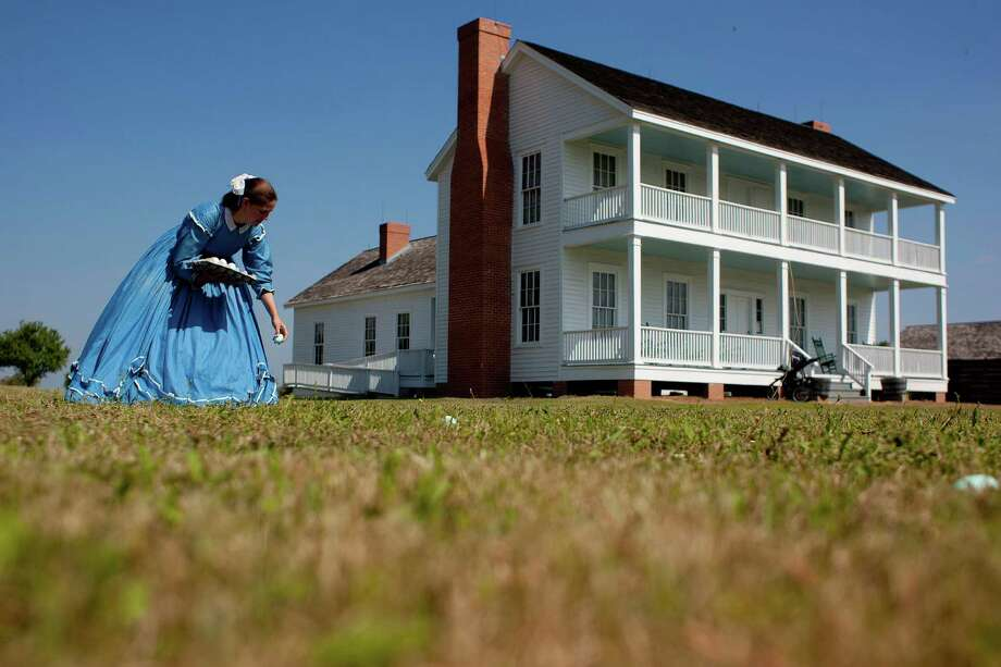 Dressed in an 1860s hoop dress, Leslee Gupton hides Easter eggs outside the 1860s Ryon Prairie Home at the George Ranch Historical Park Saturday, April 19, 2014, in Houston. Children were able to step back in time and participate in an old fashion Easter egg hunt, play games and decorate eggs. Photo: Johnny Hanson, Houston Chronicle / © 2014  Houston Chronicle