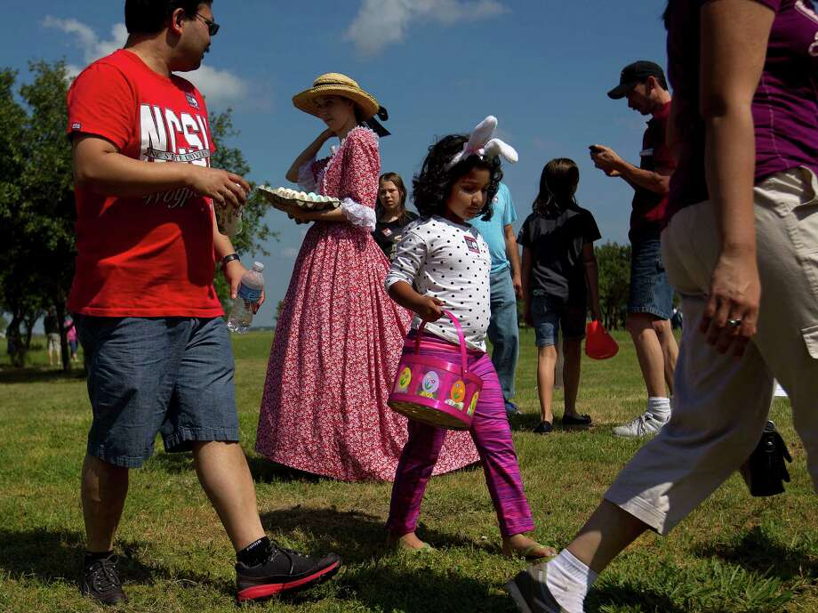 Next to his daughter, Gauri, 6, who was looking for Easter eggs, Supriyo Ghosh, looks back at Kimberly Weglarz, dressed in a dress from the 1800s during an old-fashioned Easter egg hunt outside the1860s Ryon Prairie Home at the George Ranch Historical Park Saturday, April 19, 2014, in Houston. Children were able to step back in time and play games popular in the 1800s and decorate eggs. Photo: Johnny Hanson, Houston Chronicle / © 2014  Houston Chronicle