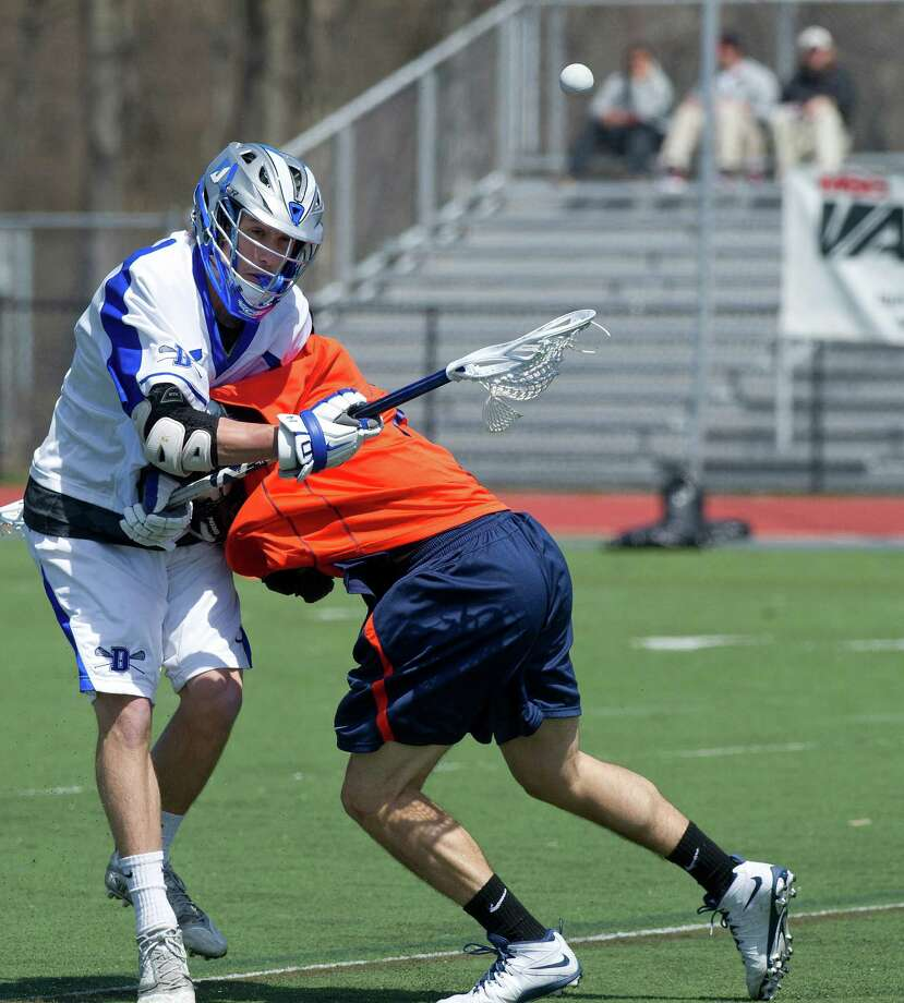 Darien's Peter Lindley loses control of the ball as he is checked by Manhassett's Jack Miller during Saturday's boys lacrosse game in Darien, Conn., on April 19, 2014. Photo: Lindsay Perry / Stamford Advocate