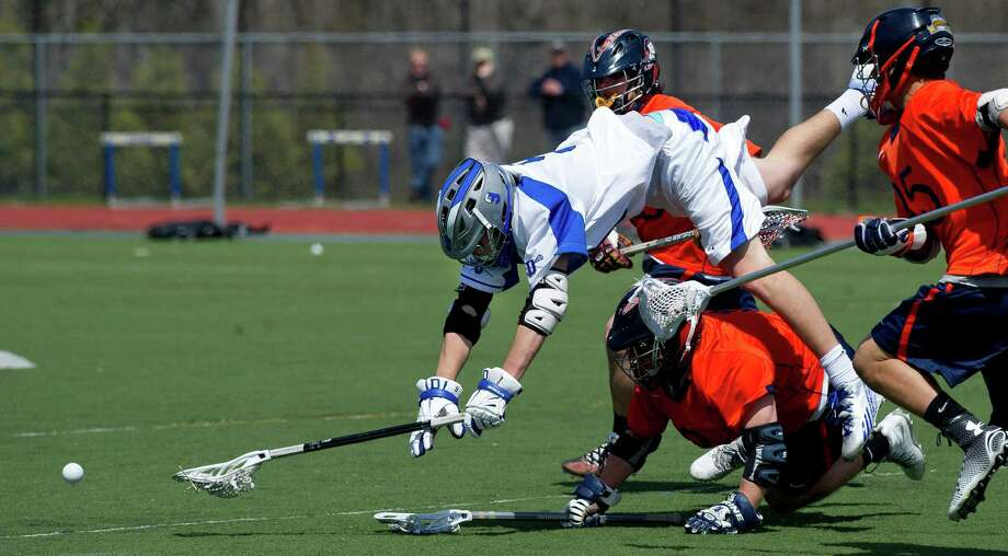 Darien's Owen Koorbusch dives over Manhassett's Ryan Miller in an attempt to gain control of the ball during Saturday's boys lacrosse game in Darien, Conn., on April 19, 2014. Photo: Lindsay Perry / Stamford Advocate