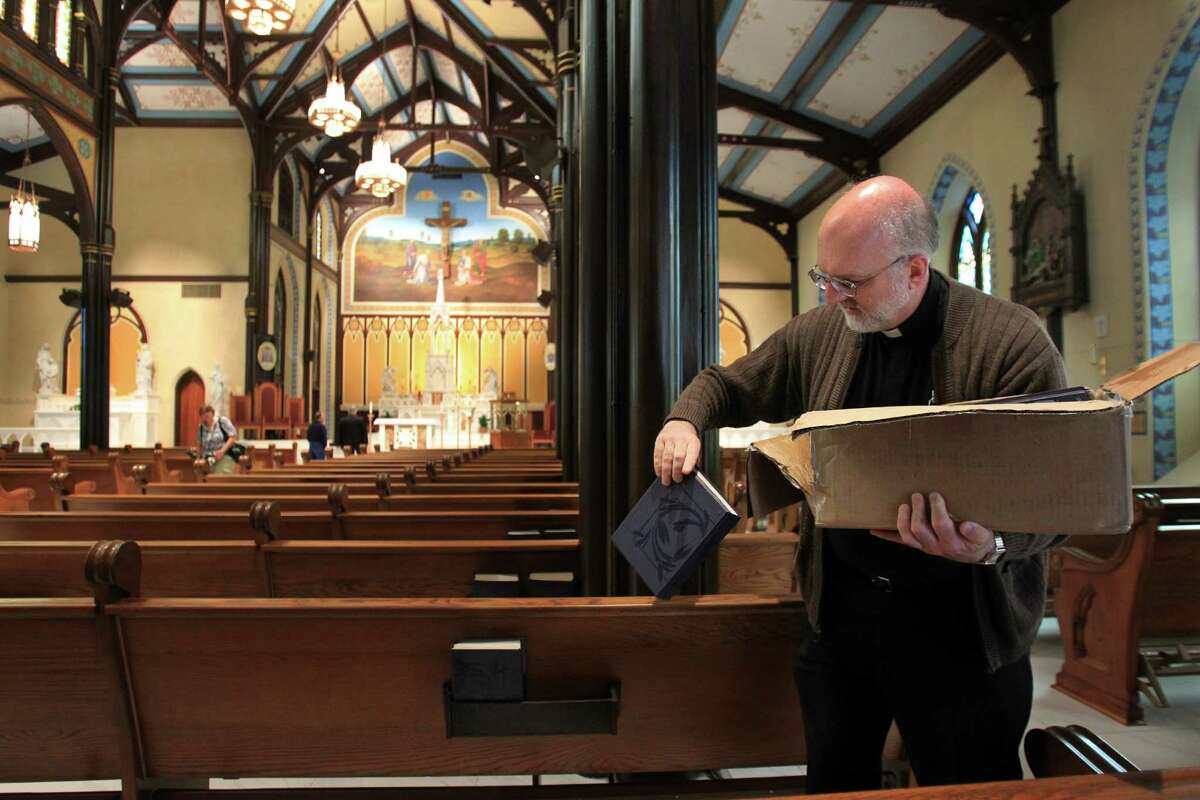 Father E.J. Stein distributes hymn books in preparation for Easter Sunday Mass in the newly restored St. Mary Cathedral Basilica on April 17, 2014, in Galveston, Tx.