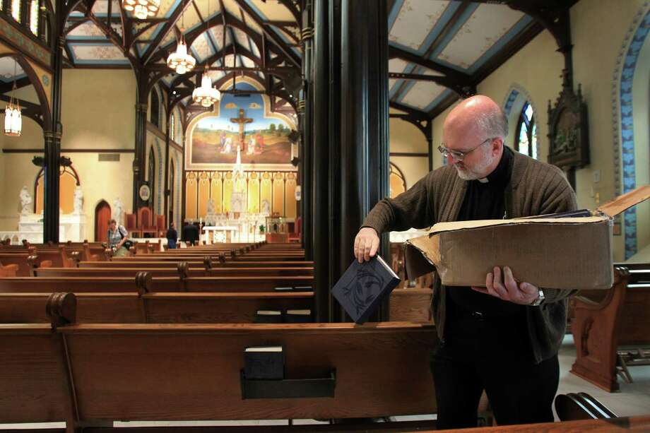 Father E.J. Stein distributes hymn books in preparation for Easter Sunday Mass in the newly restored St. Mary Cathedral Basilica on April 17, 2014, in Galveston, Tx. Photo: Mayra Beltran, Houston Chronicle / © 2014 Houston Chronicle