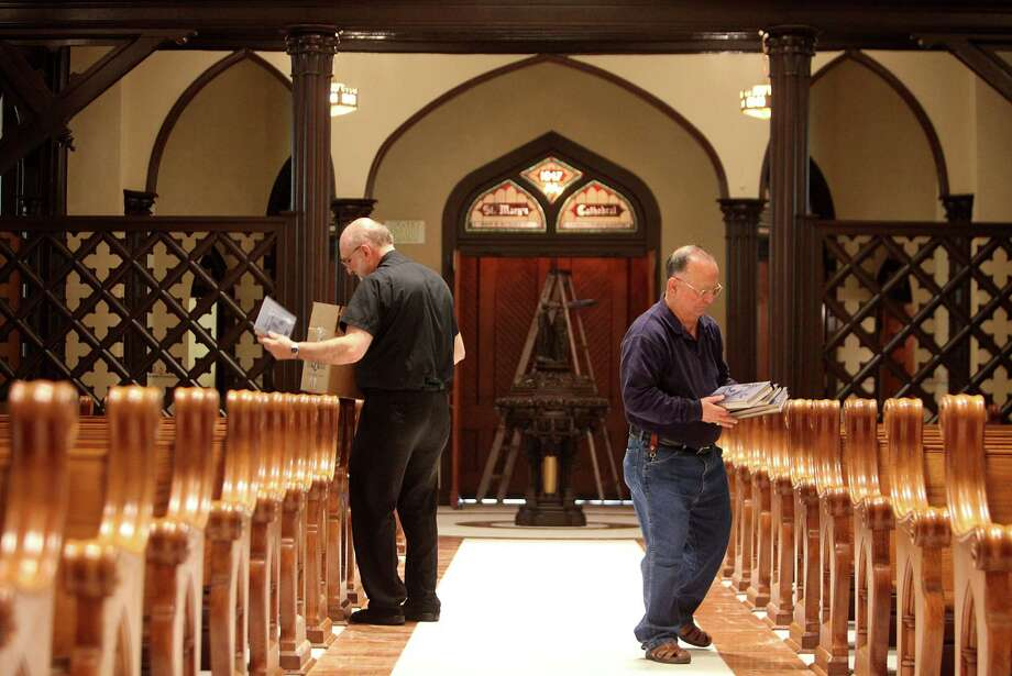 Father E.J. Stein and Deacon John Pisone distribute hymn books in preparation for Easter Sunday Mass at the newly restored St. Mary Cathedral Basilica on April 17, 2014, in Galveston, Tx. Photo: Mayra Beltran, Houston Chronicle / © 2014 Houston Chronicle