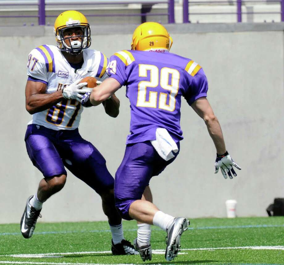 Wide Receiver Cole King (87) makes a catch while being defended by cornerback Anthony DeLuca (29) during the first half of Ualbany's Purple-White spring NCAA college football game on Saturday, April 19, 2014, in Albany, N.Y., (Hans Pennink) ORG XMIT: HP101 Photo: HANS PENNINK