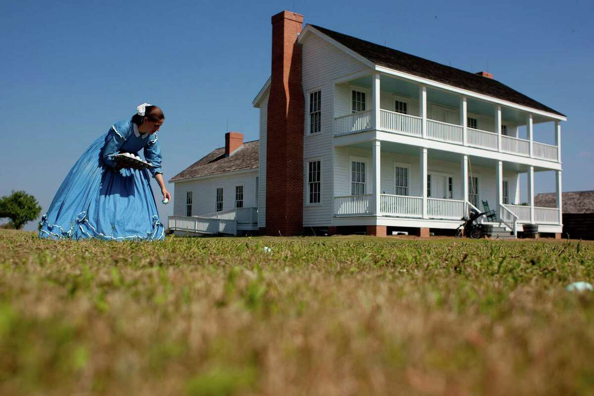 Leslee Gupton hides Easter eggs outside the 1860s Ryon Prairie Home at the George Ranch Historical Park on Saturday. The park hosted an Easter egg hunt that took children back to an earlier time.