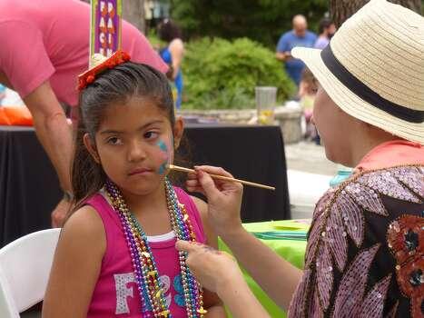 Alex Graham paints the face of Analisa Martin del Campo during the Fiesta Arts Fair on Saturday, April 18, 2014. Photo: Billy Calzada, San Antonio Express-News /  San Antonio Express-News