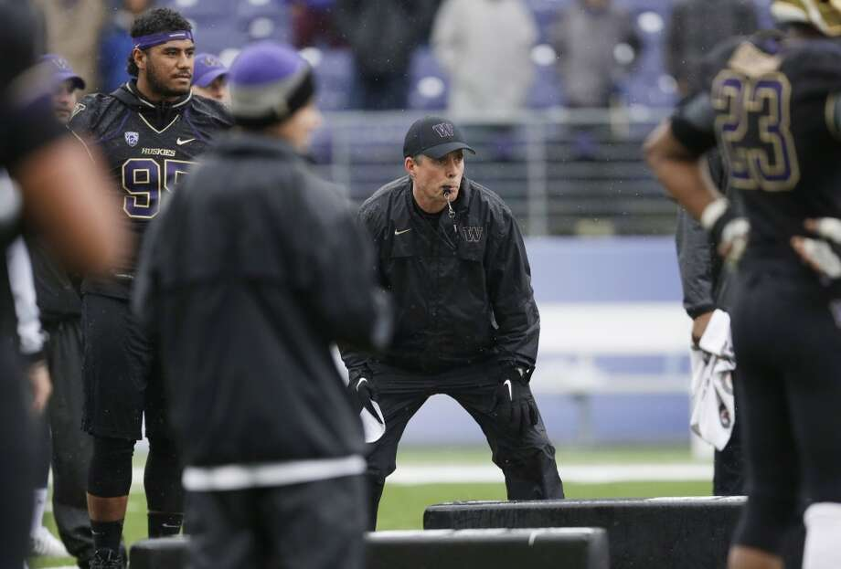 Washington coach Chris Petersen watches a drill, Saturday, April 19, 2014, during the NCAA college football team's spring preview in Seattle. The team held an open practice and limited scrimmag. (AP Photo/Ted S. Warren) Photo: Ted S. Warren, Associated Press