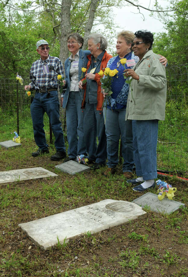 Family members prepare to place yellow roses on the graves in the Foley Cemetery in Hallettsville. Photo: Jerry Baker, For The Chronicle