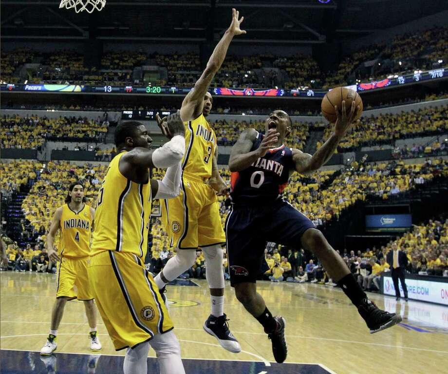 Atlanta Hawks' Jeff Teague shoots against Indiana Pacers' Roy Hibbert and George Hill (3) during the first half in Game 1 of an opening-round NBA basketball playoff series on Saturday, April 19, 2014, in Indianapolis. (AP Photo/Darron Cummings) Photo: Darron Cummings, Associated Press / AP