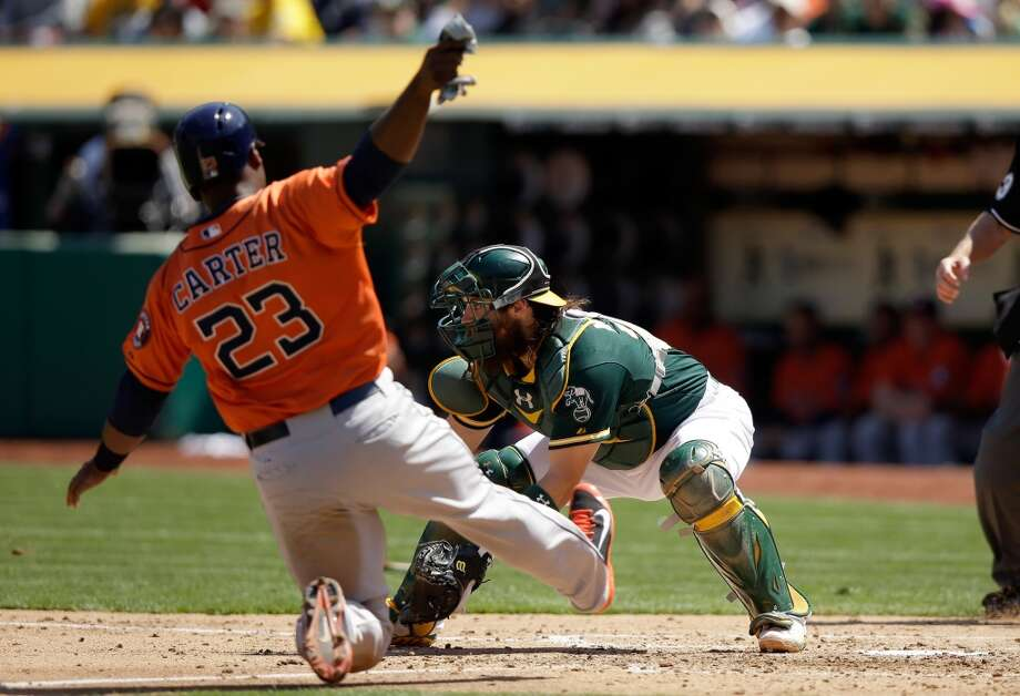Chris Carter #23 of the Astros slides past Derek Norris #36 of the Athletics to score on a single by Matt Dominguez. Photo: Ezra Shaw, Getty Images
